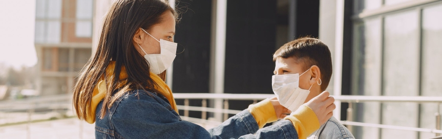 Girl helps brother put on a medical mask