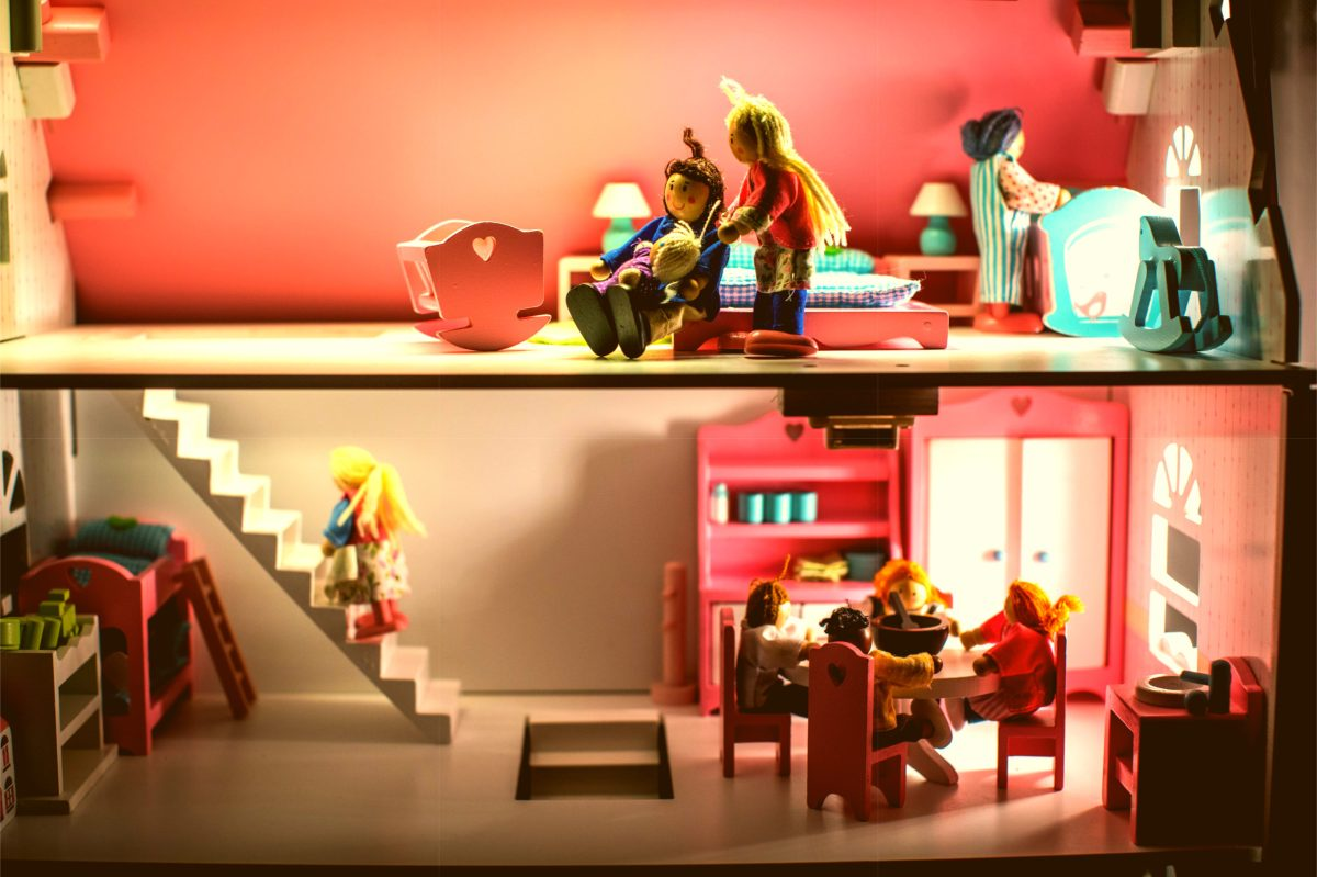 Colorful dollhouse with a family of wooden dolls