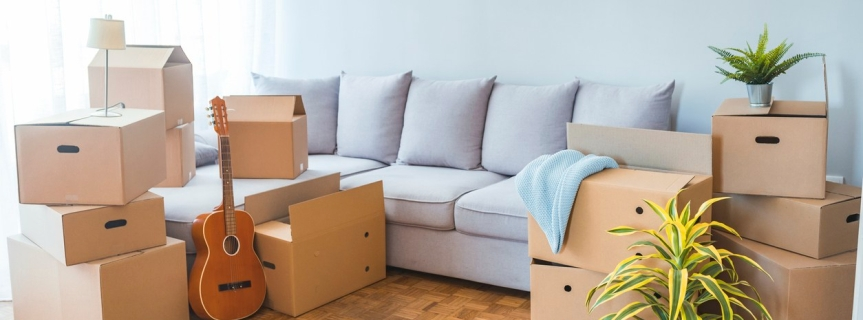 Moving day, cardboard carton boxes stacked with household belongings in modern living room, packed containers on floor in new home.