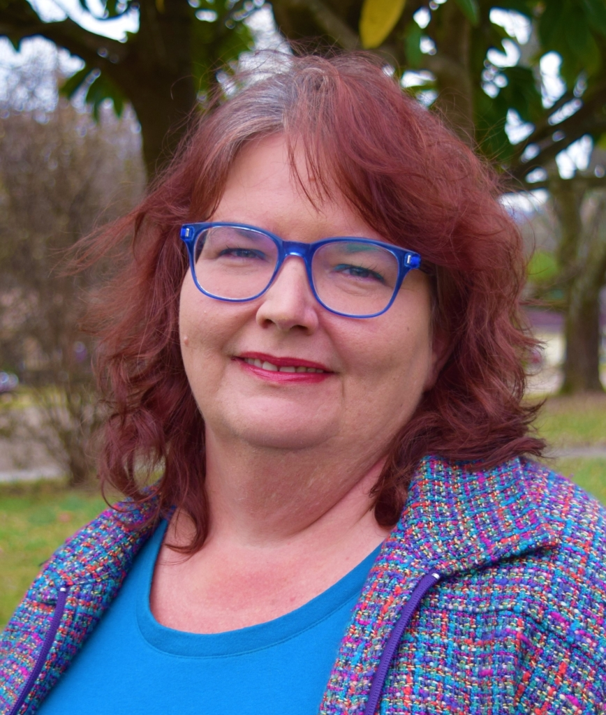 White woman between the ages of 40 and 55, wearing a bright colored raw tweed zip-up jacket over a bright cyan blue t-shirt. She has dyed dark auburn hair, and glasses with bright true blue rims. She is smiling and looks friendly, caring, and warm-hearted.