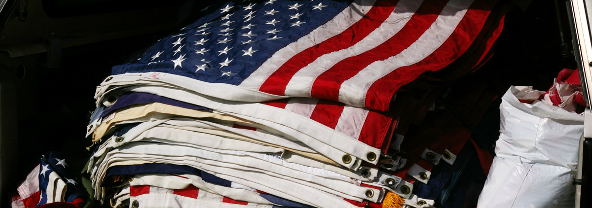 Neatly stacked pile of many old, worn out, sometimes discolored or tattered American flags.